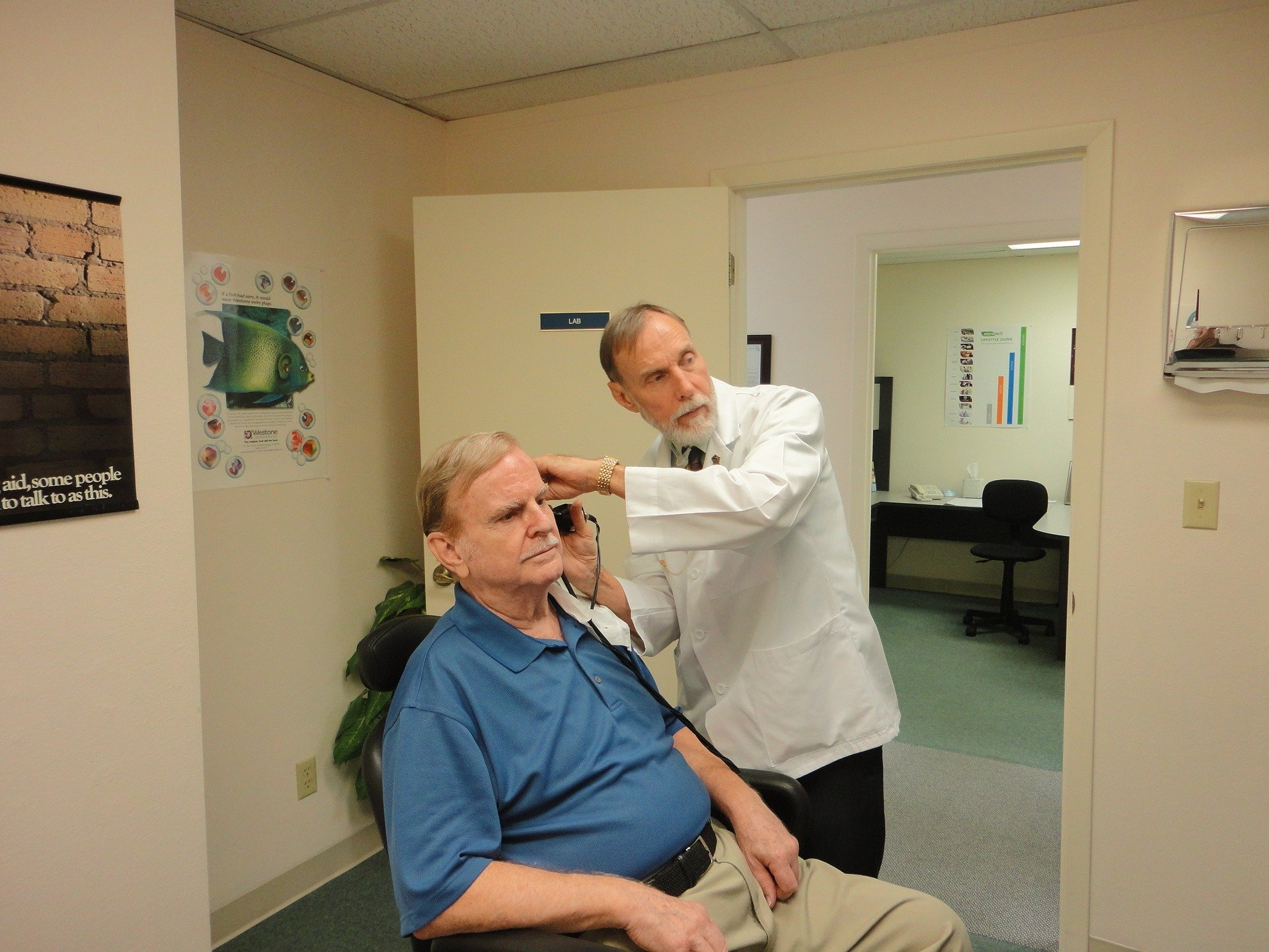 An elderly man having his ears tested by a doctor   Photo: Pixabay/williamsje1