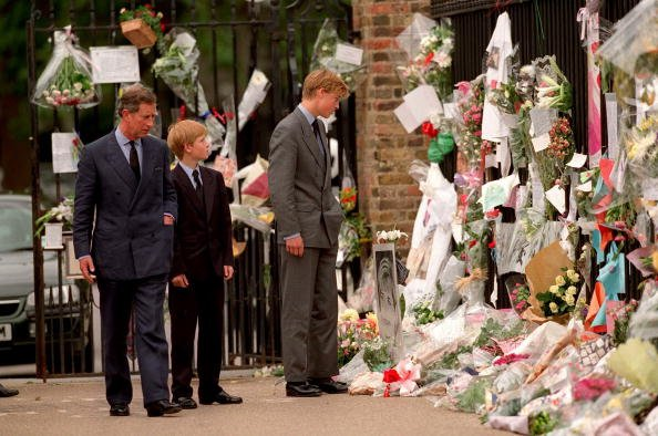 Le prince de Galles, le prince William et le prince Harry examinent des hommages floraux à Diana, princesse de Galles devant le palais de Kensington le 5 septembre 1997 à Londres, en Angleterre. | Photo : Getty Images.