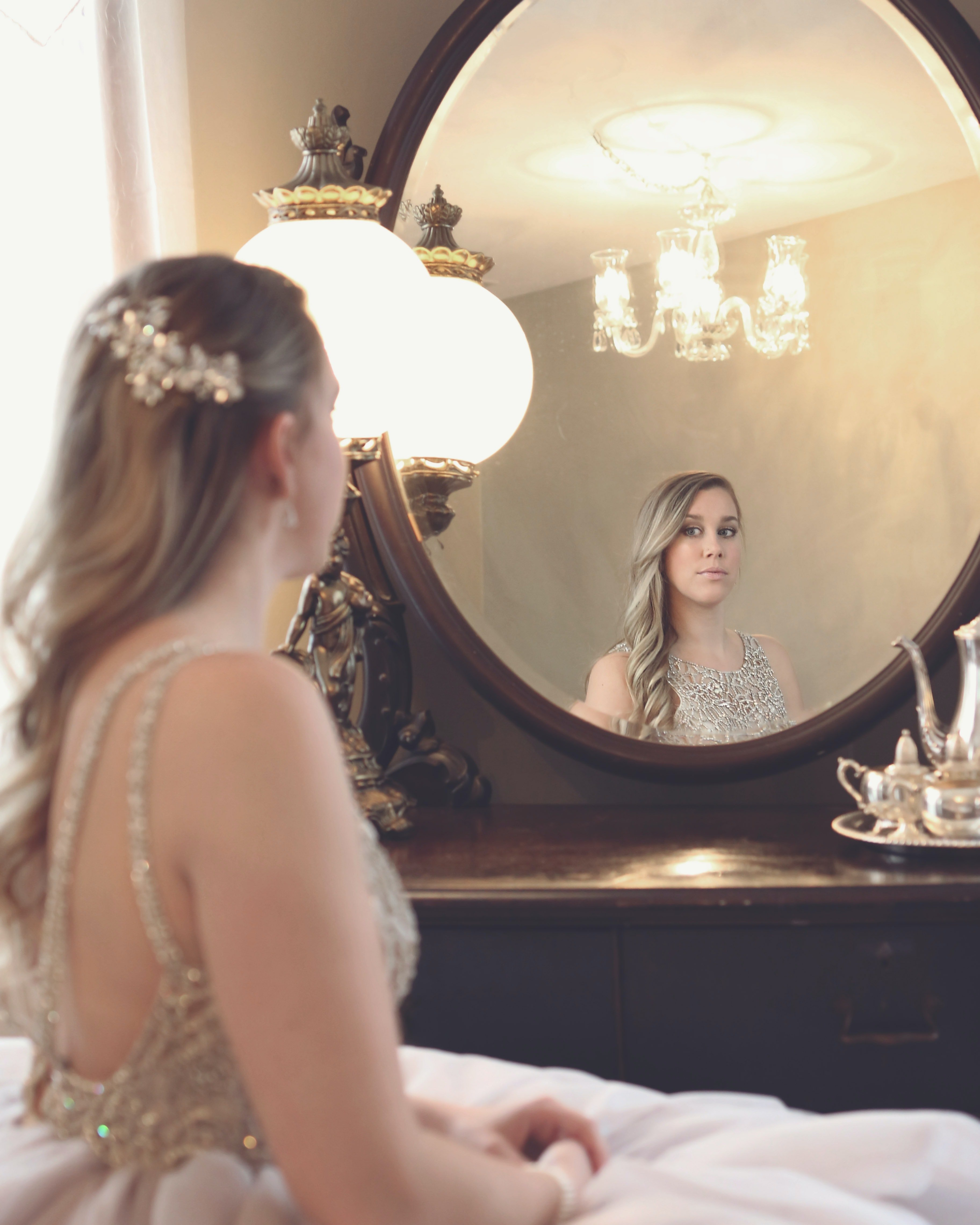 A woman staring at the mirror. | Photo: Pexel