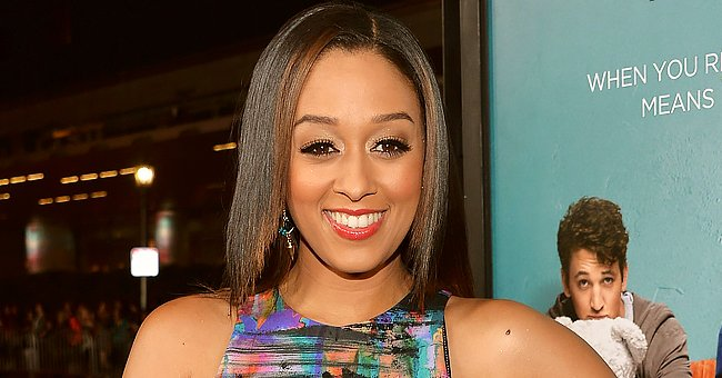 Tia Mowry Makes Hearts Go Wild Posing Next to a Car in a Black Silk Dress & Zebra-Print Heels