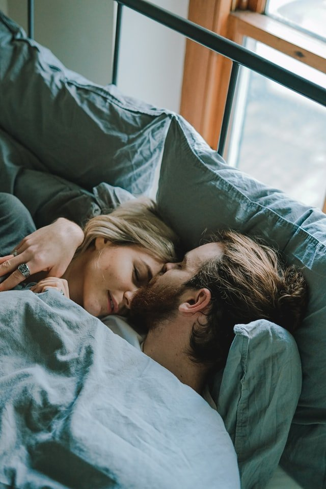 Men kissing woman on forehead while laying in bed | Source: Unsplash