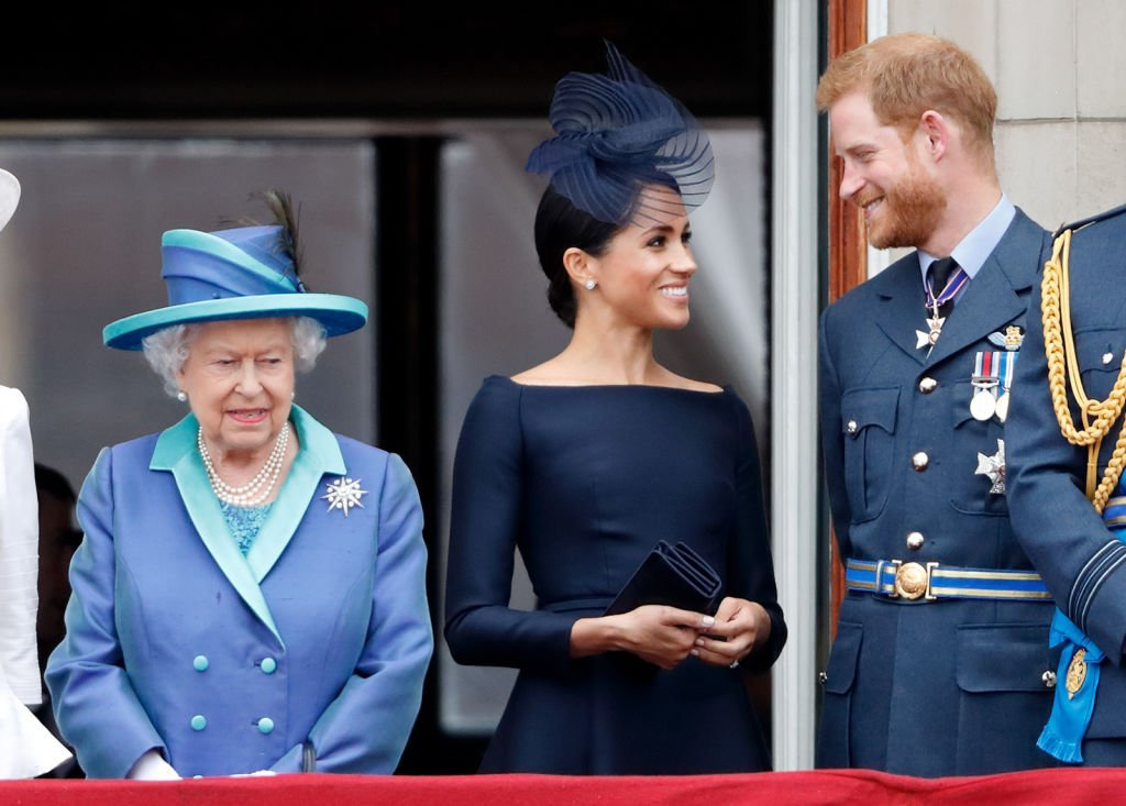 Queen Elizabeth, Meghan Markle and Prince Harry stand on the balcony at Buckingham Palace to watch a flypast that marked the centenary of the Royal Air Force on July 10, 2018, in London, England | Source: Max Mumby/Indigo/Getty Images