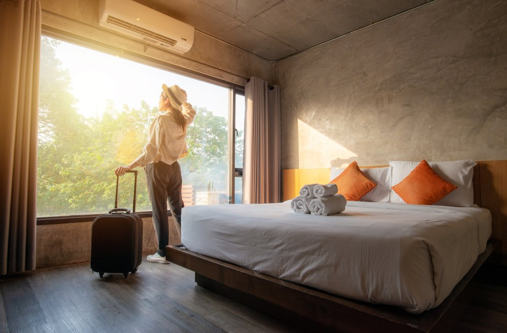 Portrait of tourist woman standing nearly window, looking to beautiful view with her luggage in hotel bedroom after check-in. Conceptual of travel and vacation   Photo: Shutterstock