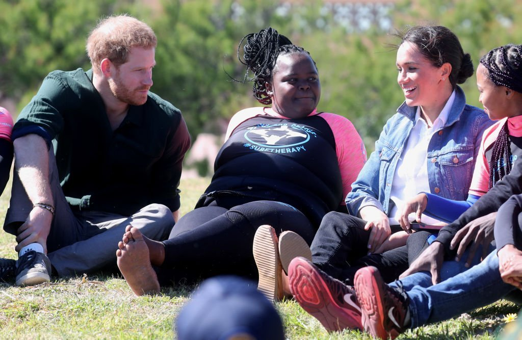 Prince Harry and Meghan join surf mentors and participate in a group activity as they visited Waves for Change, an NGO, at Monwabisi Beach. | Source: Getty Images