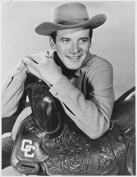 Peter Breck wears a cowboy outfit and leans on a saddle, circa 1950s. | Photo: Getty Images
