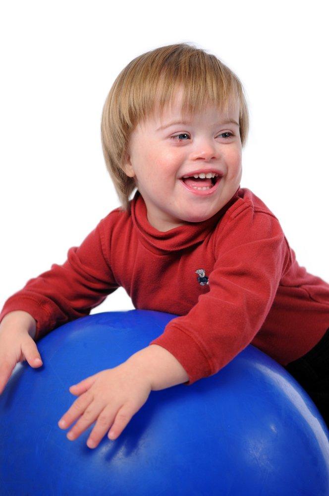 Niño con síndrome de Down sonriente jugando con una pelota. Fuente: Shutterstock.