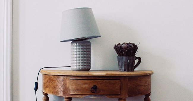 Lamp resting on a wooden table | Photo:  unsplash.com/Michal Balog