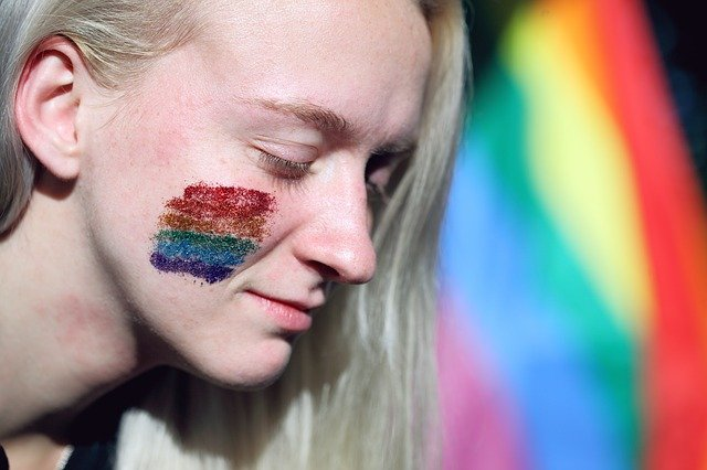 A woman attends a LGBT pride parade with the rainbow flag painted with glitter on her face. I Image: Getty Images.