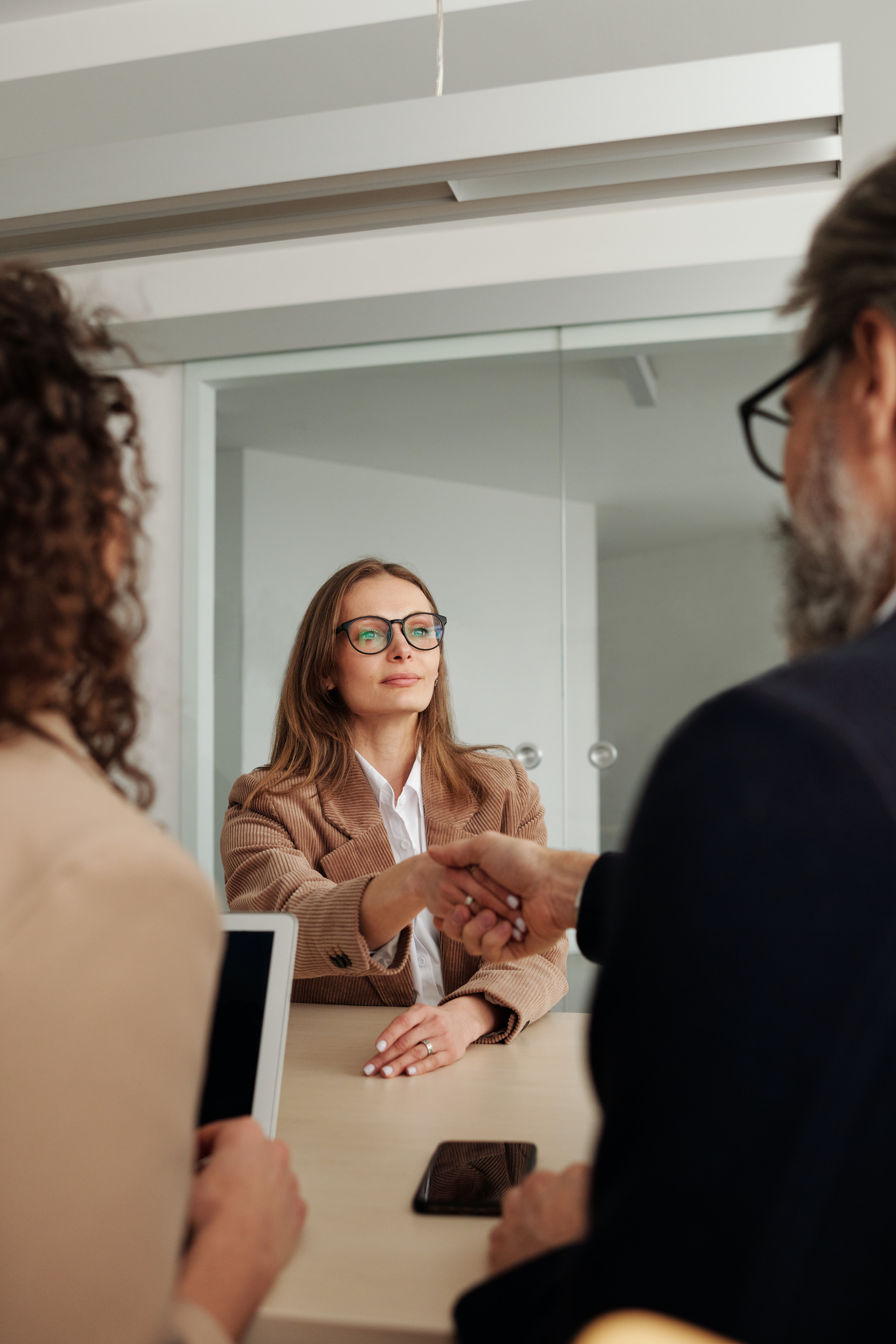 A woman in a suit and glasses shaking hands with a woman across her   Source: Pexels