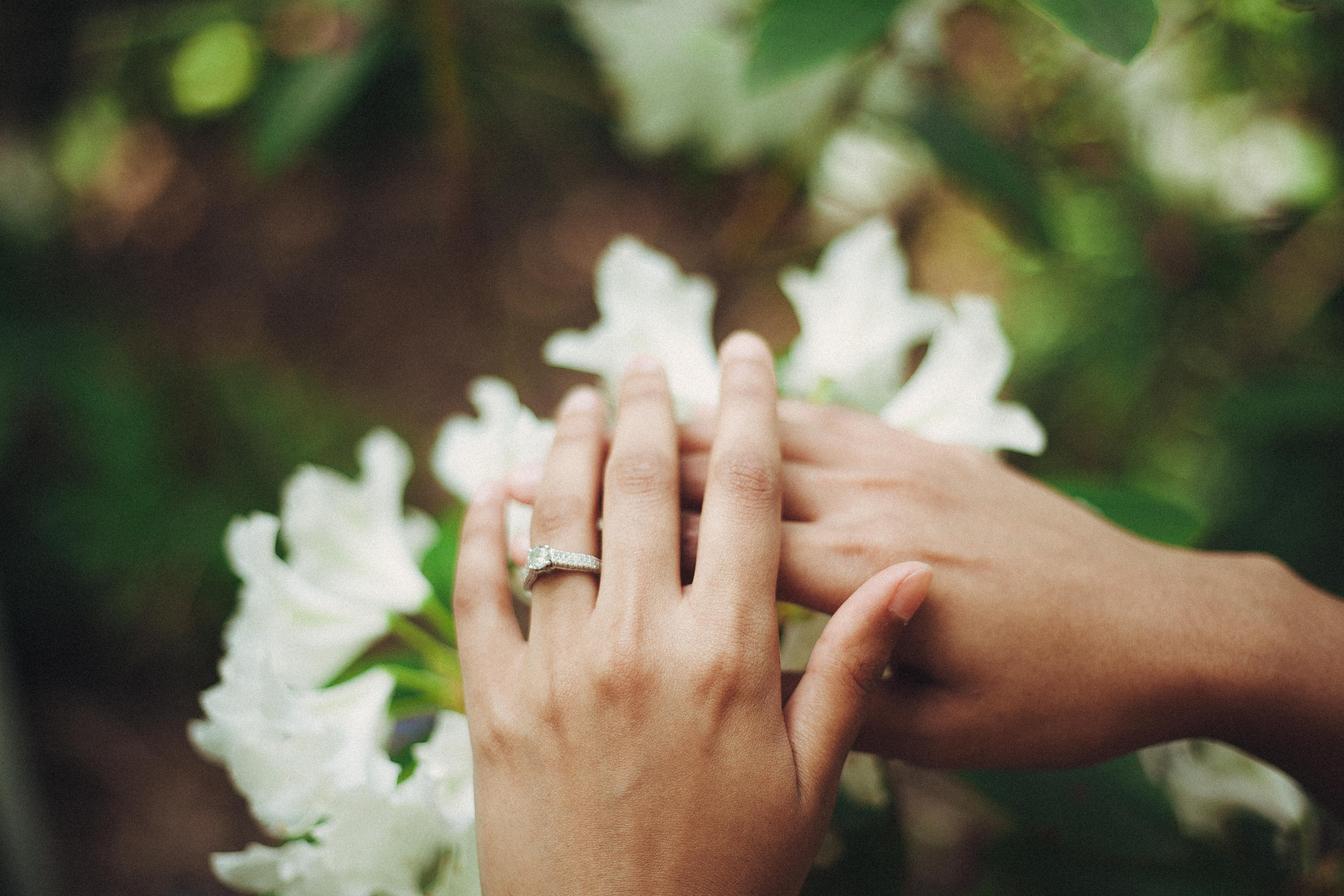 A woman's hand with an engagement ring   Photo: Pexels