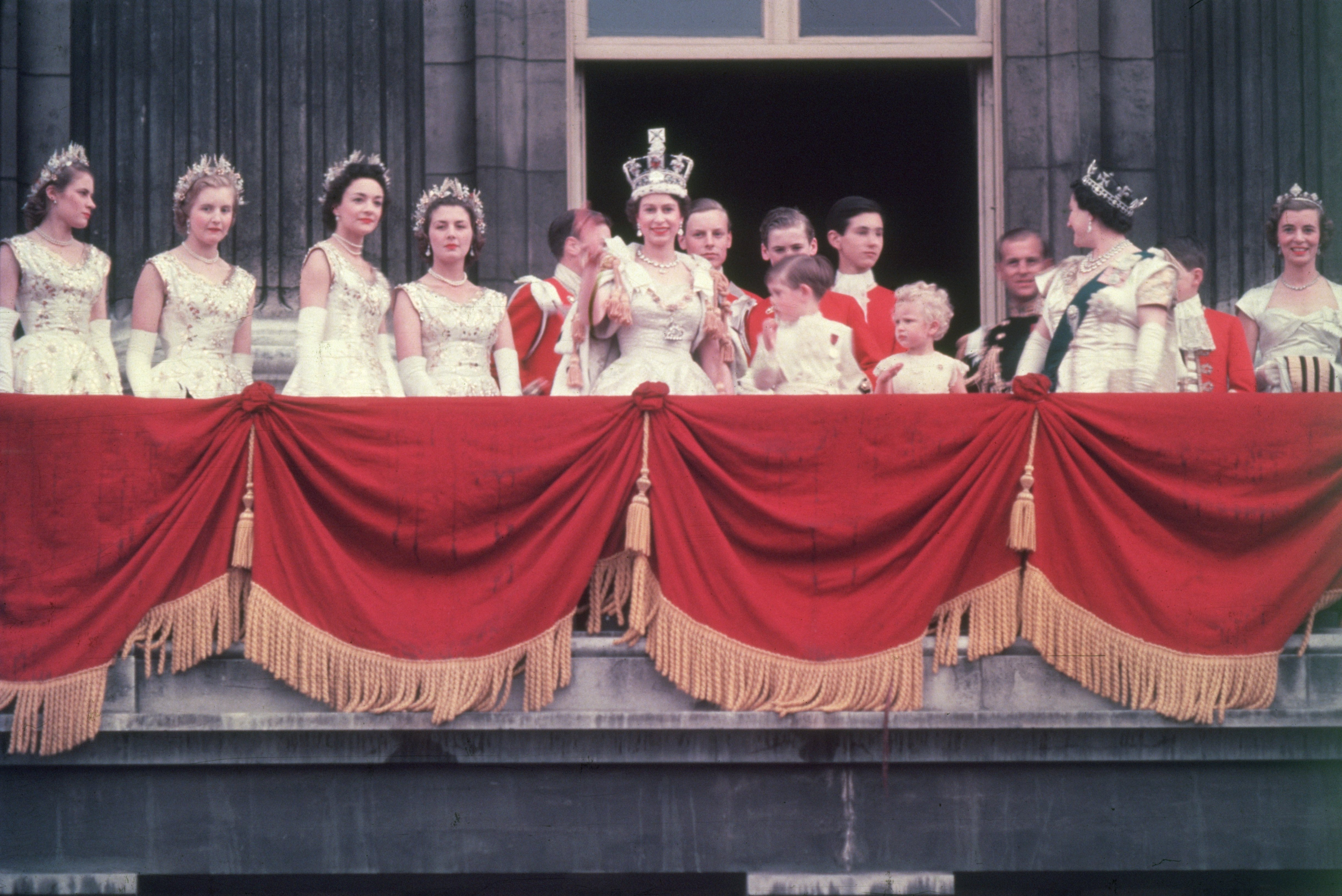 The newly crowned Queen Elizabeth II waves to the crowd from the balcony at Buckingham Palace. Her children Prince Charles and Princess Anne stand with her in 1953 | Photo: Getty Images
