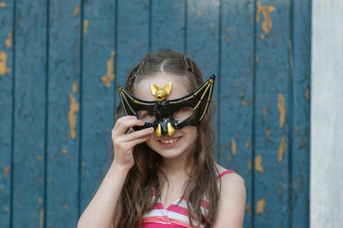 A young girl with a bat inspired Halloween mask. | Source: Shutterstock.