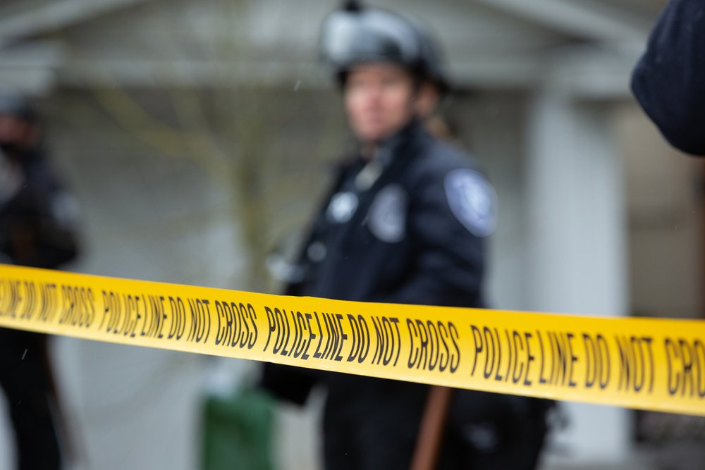 """""""Police Line Do No Cross"""" caution tape, with a law enforcement officer in the blurry background 