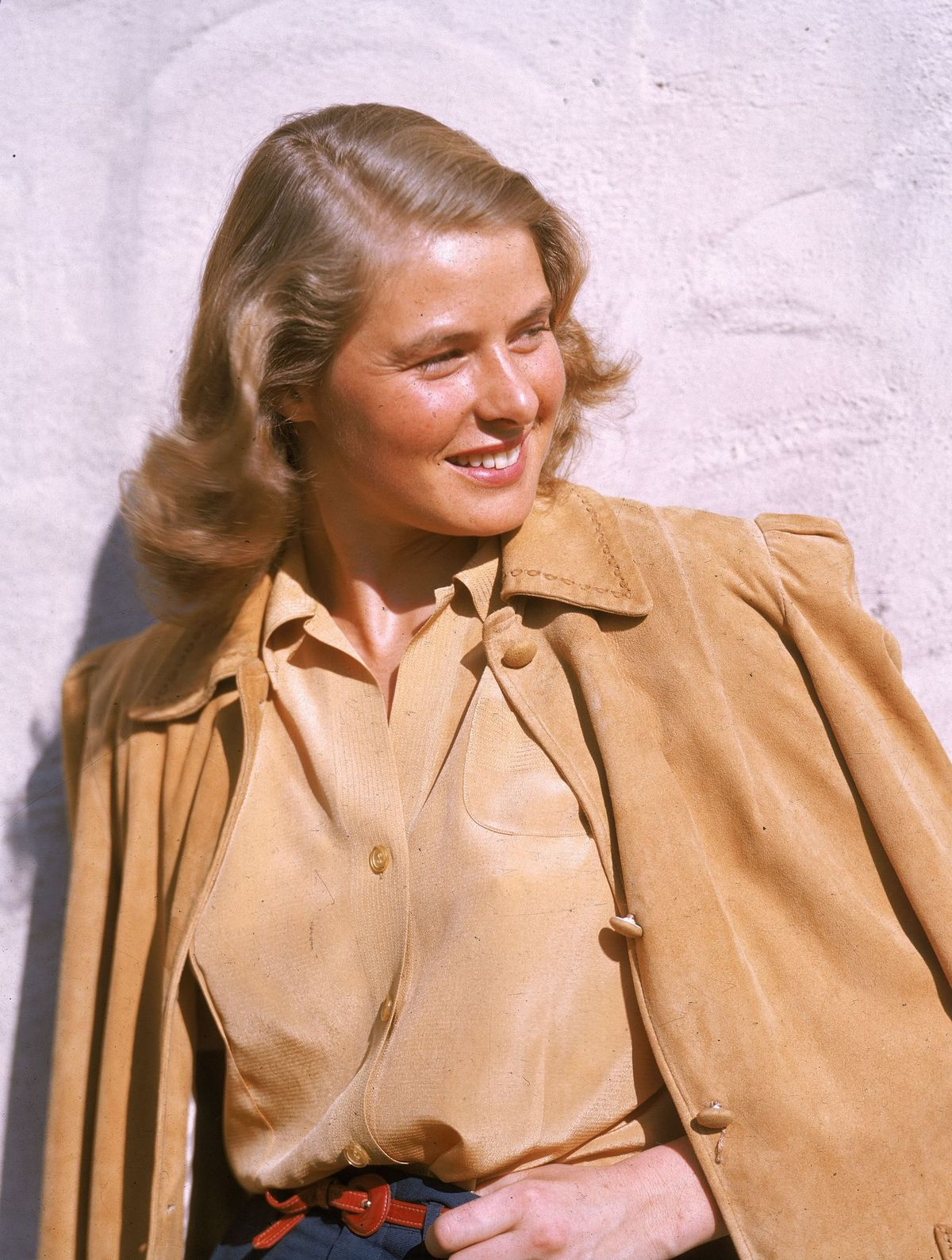 Ingrid Bergman smiles as she poses outdoors, wearing a tan leather jacket, on January 1, 1945. | Photo: Getty Images