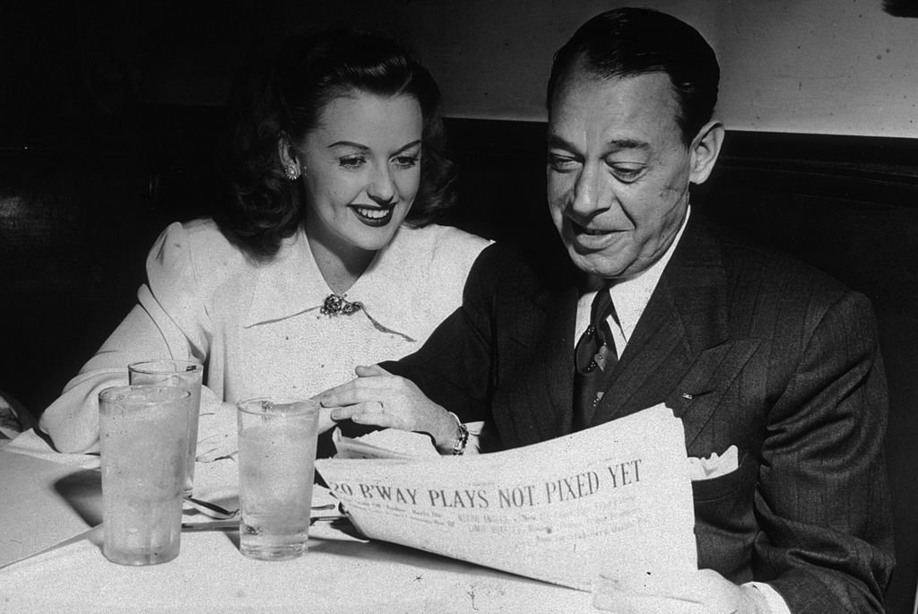 Joe E. Lewis  and Martha Stewart sitting side by side in a booth on January 01, 1946 | Photo: Getty Images