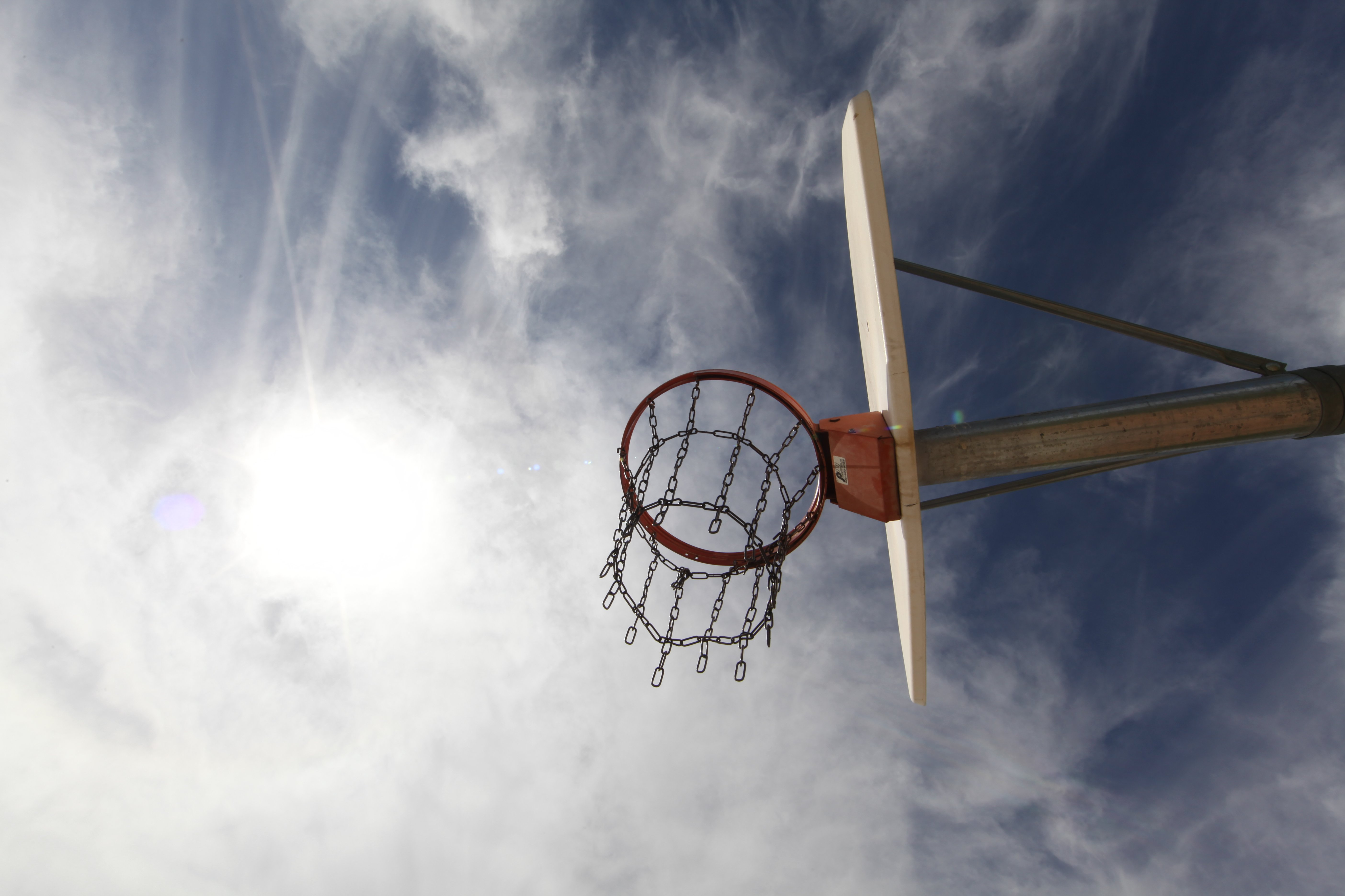A basketball hoop in a court.   Source: Pexels
