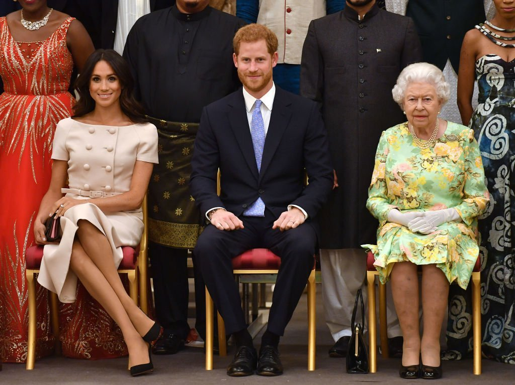 Meghan, Duchess of Sussex, Prince Harry, Duke of Sussex and Queen Elizabeth II at the Queen's Young Leaders Awards Ceremony at Buckingham Palace | Photo: Getty Images