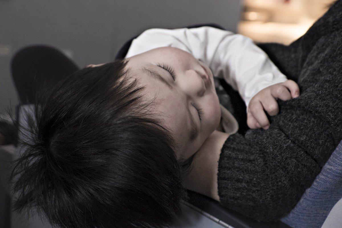 Un bébé dans les bras d'un adulte. l Source: PxHere