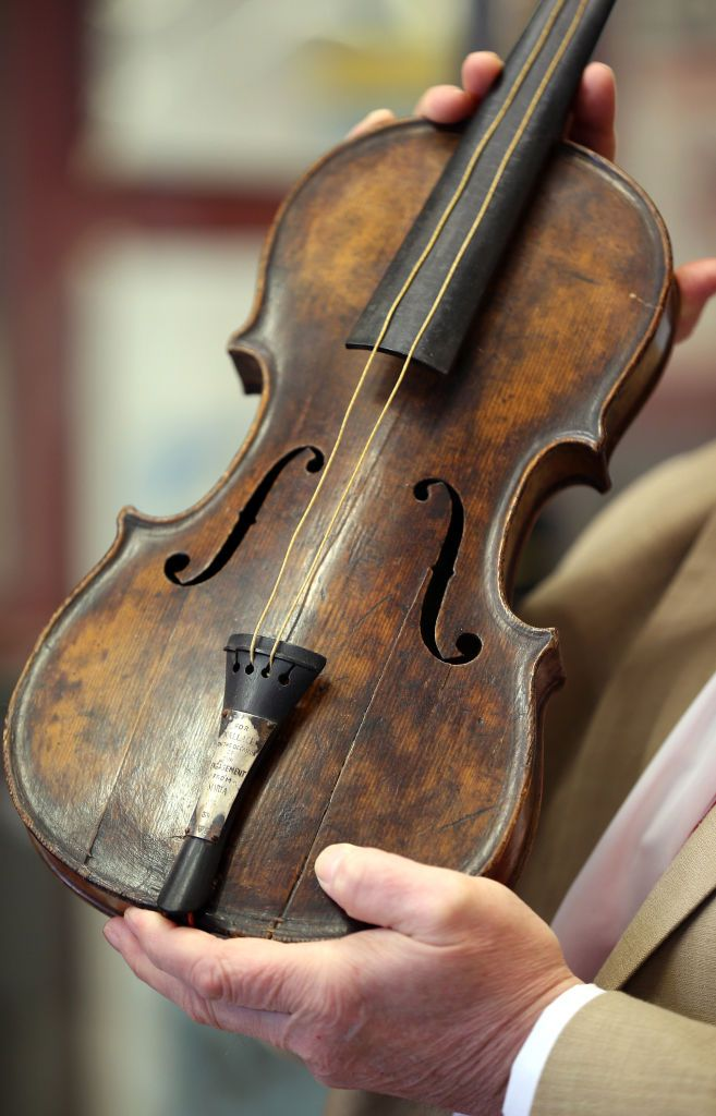 A man holding up a violin. | Source: Shutterstock
