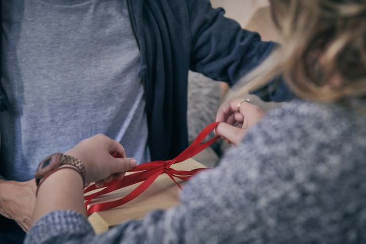 Woman tying red ribbon | Photo: Getty Images
