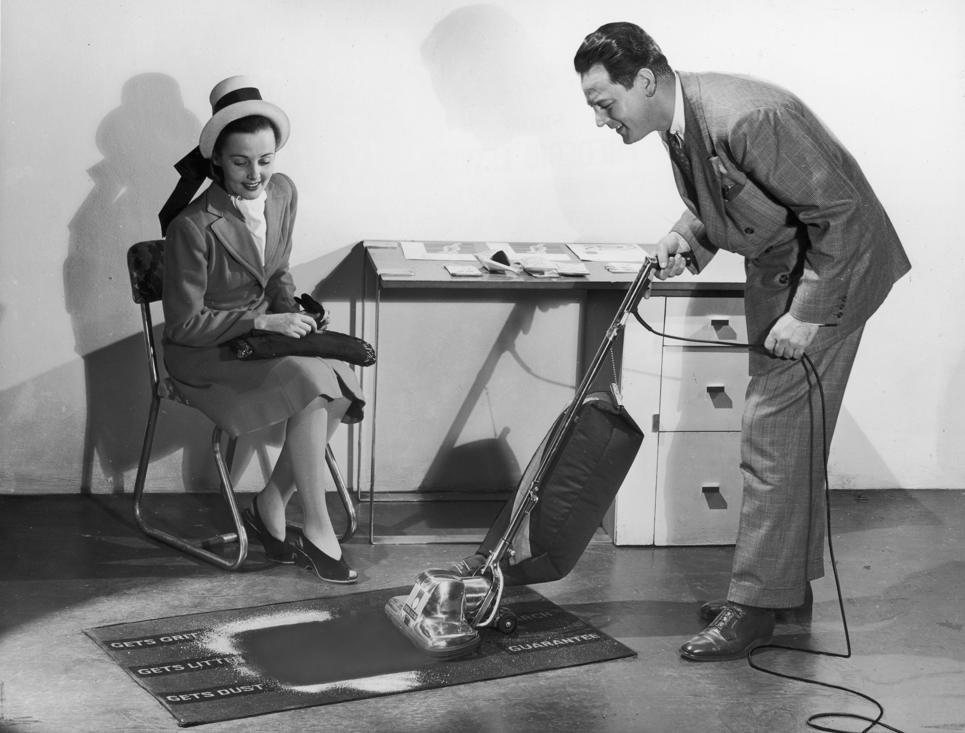 A salesman demonstrates the effectiveness of a General Electric vacuum cleaner to a prospective customer. | Photo: Getty Images