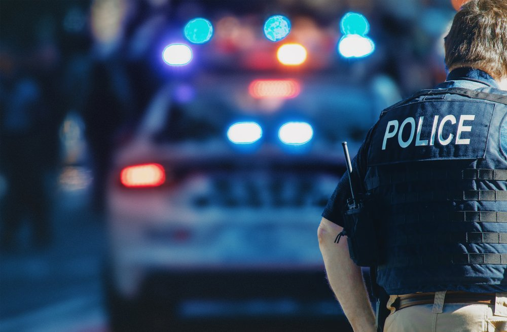 An American policeman walks in the street with a police car visible in the background | Photo: Shutterstock/ALDECA studio