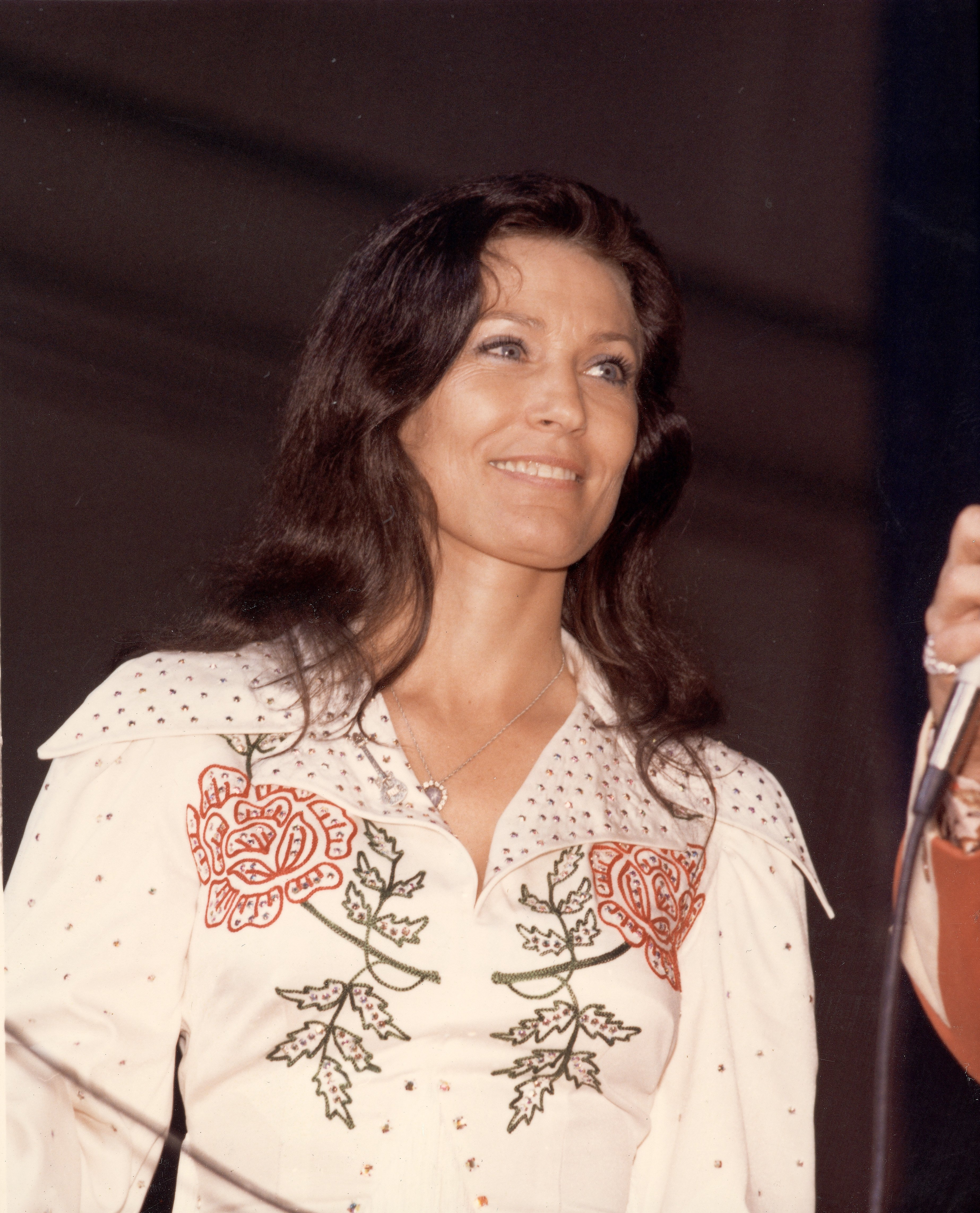 Country music singer Loretta Lynn holding a microphone onstage in the late 1970s | Photo: Getty Images