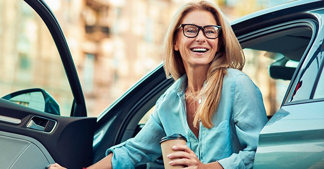 A blonde woman steps out of her car, holding a coffee cup. | Photo: Shutterstock