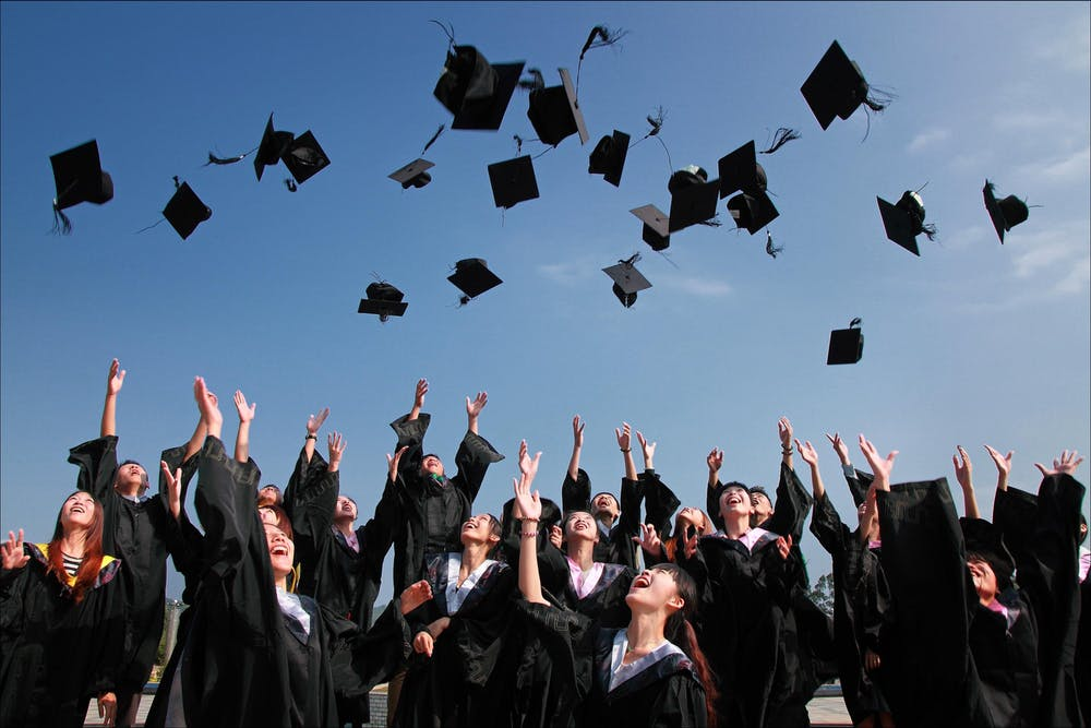 Newly graduated students throwing hats up in the air | Source: Pexels