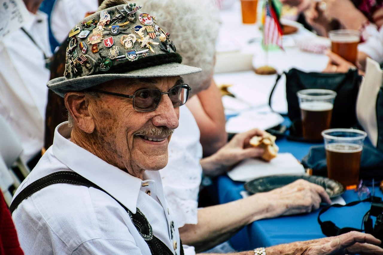Senior man smiling at a table. | Source: Brett Sayles/Pexels