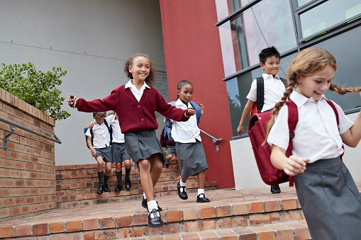 Photo of school children running and jumping off staircase from school building | Photo: Getty Images