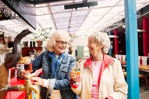 Photo of two elderly women holding wineglass and smiling while looking at each other in restaurant | Photo: Getty Images