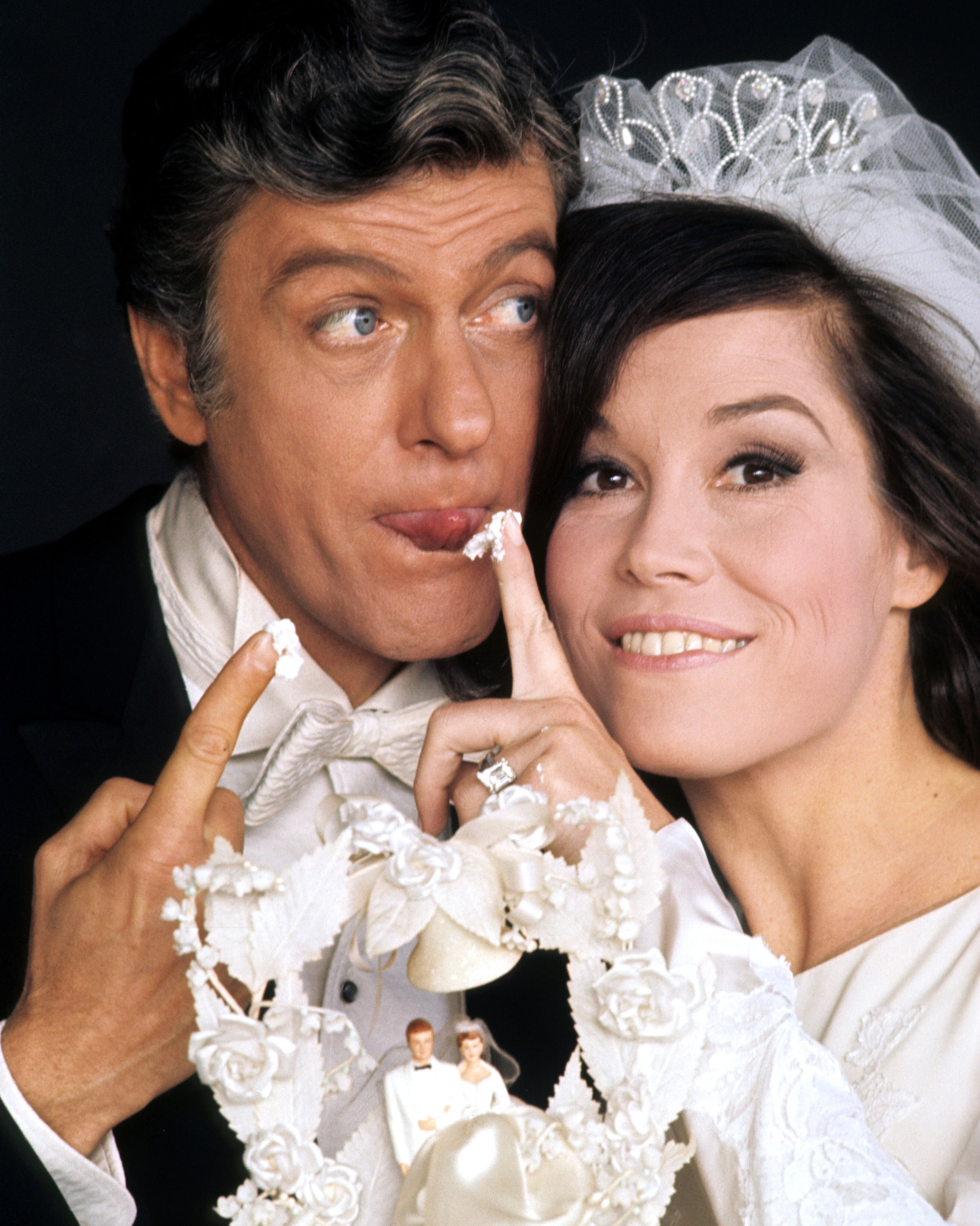 Dick Van Dyke, US actor, and Mary Tyler Moore, US actress, in a wedding dress, with a piece of icing from a wedding cake on her finger, in a publicity portrait issued for the US television special, 'Dick Van Dyke and the Other Woman', USA, 1969. | Source: Getty Images