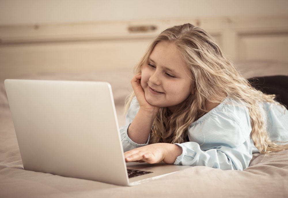 Young girl using a laptop in bed | Photo: Shutterstock