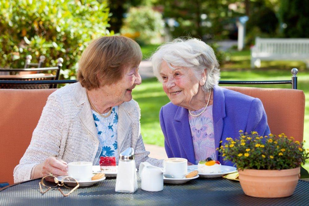 Dos mujeres mayores felices sentadas, charlando en la mesa al aire libre con café y bocadillos. Fuente: Shutterstock