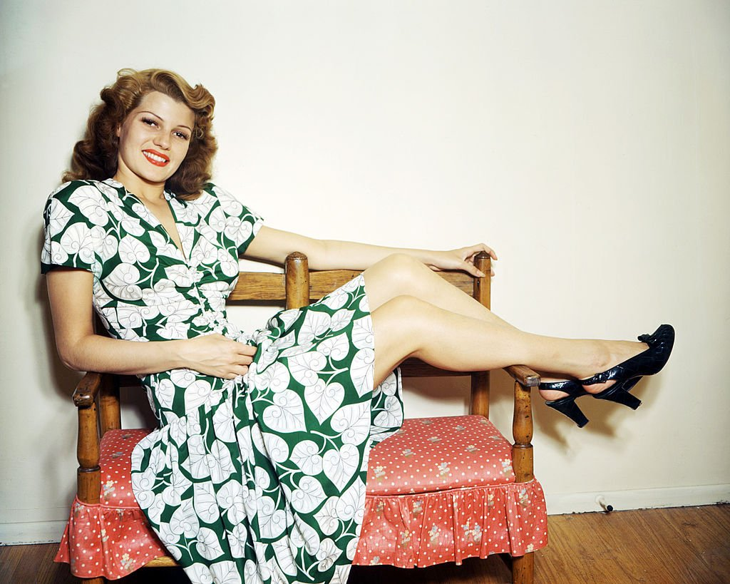 Rita Hayworth (1918 - 1987) wearing a green and white, leaf-patterned dress and putting her feet up, circa 1945.   Source: Getty Images