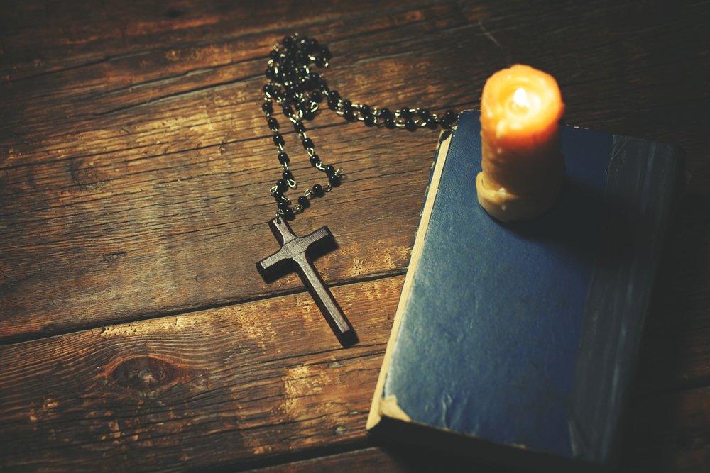 Biblia, rosario y una vela encendida.| Fuente: Shutterstock