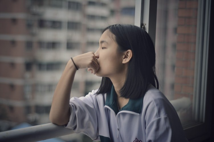 A lady in deep thought and sitting by a window. | Photo: Unsplash