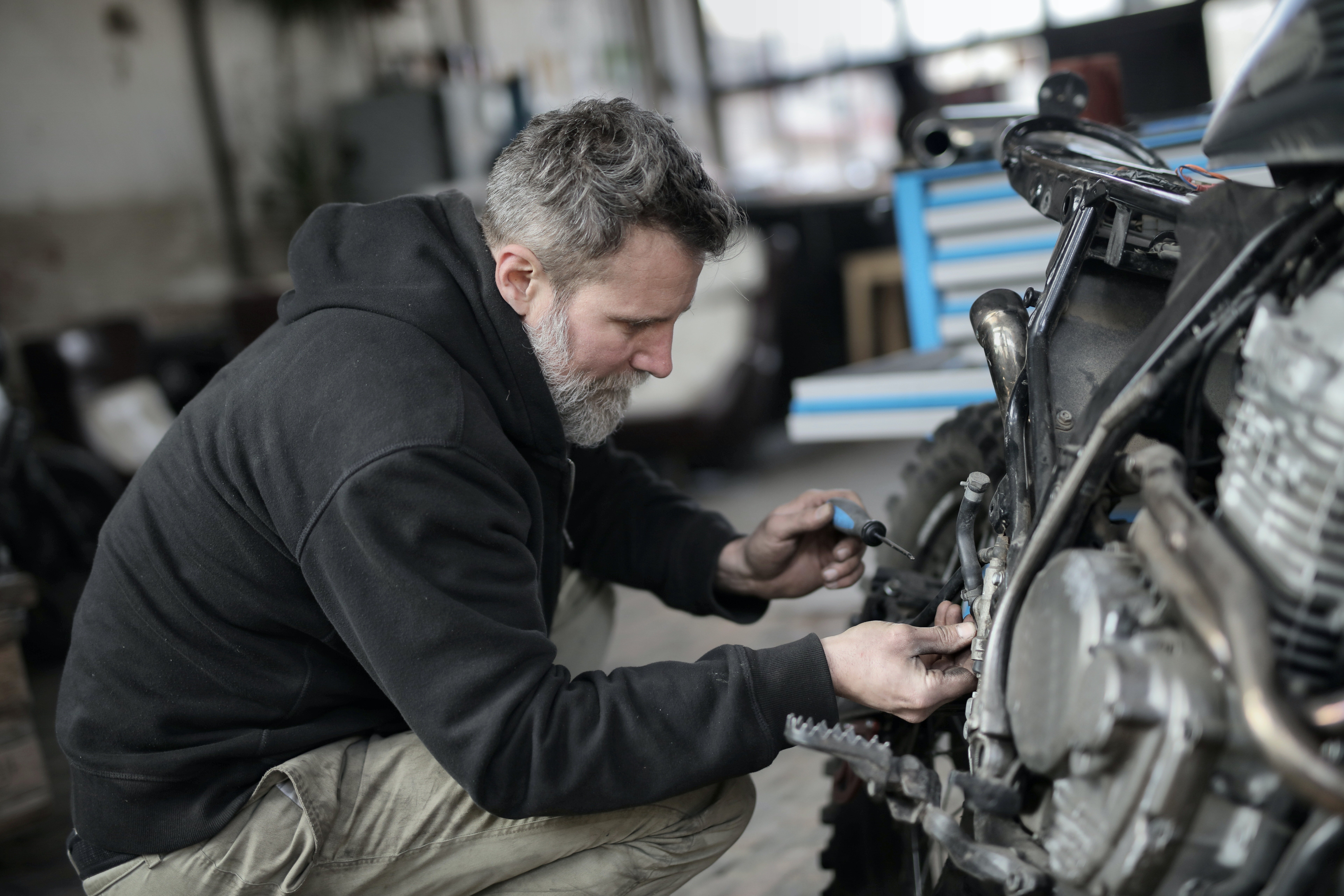 A bearded man fixing a motorcycle in a workshop. | Photo: Pexels/Andrea Piacquadio