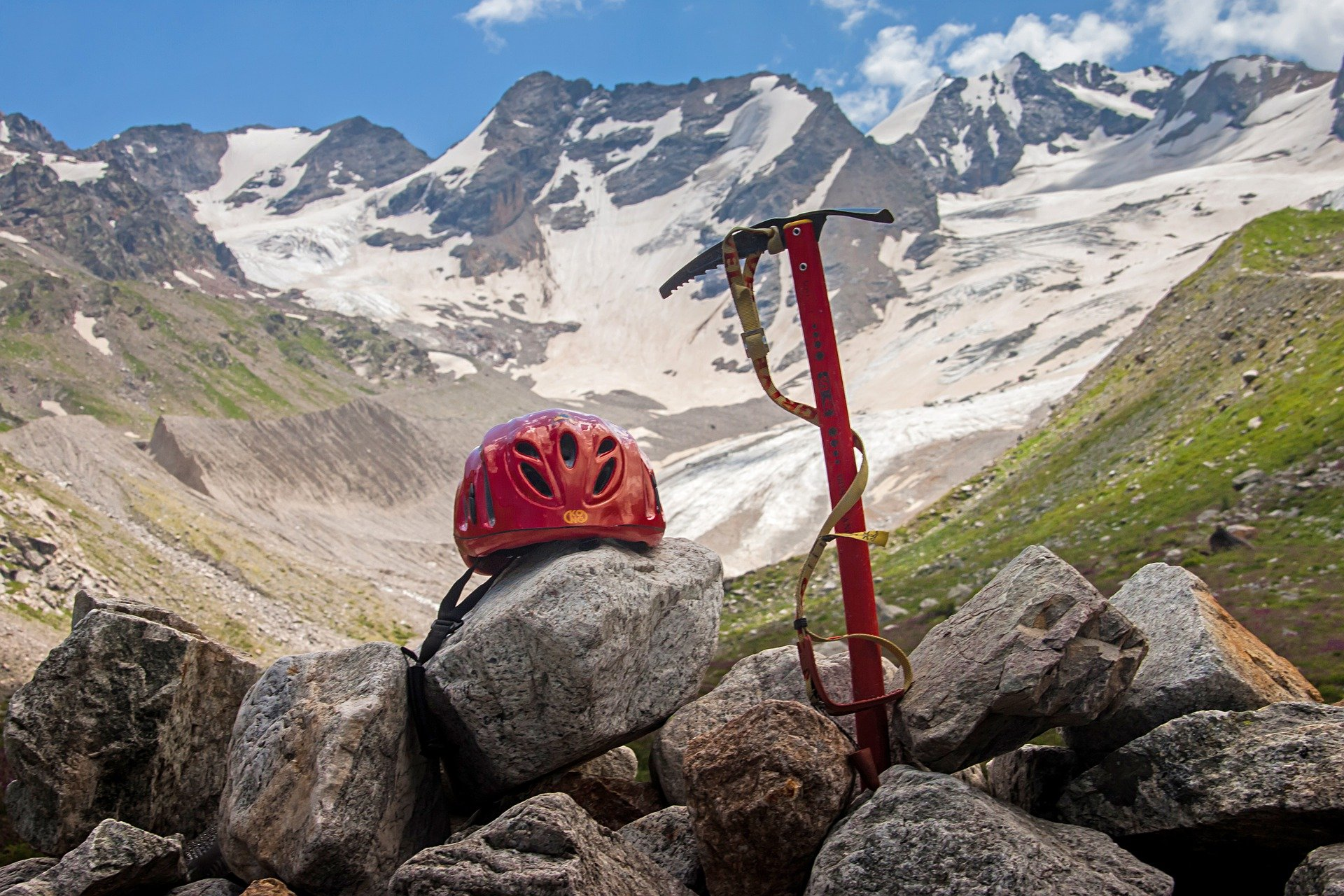 An ice pick and a helmet placed on the rocks.   Source: Pixabay.