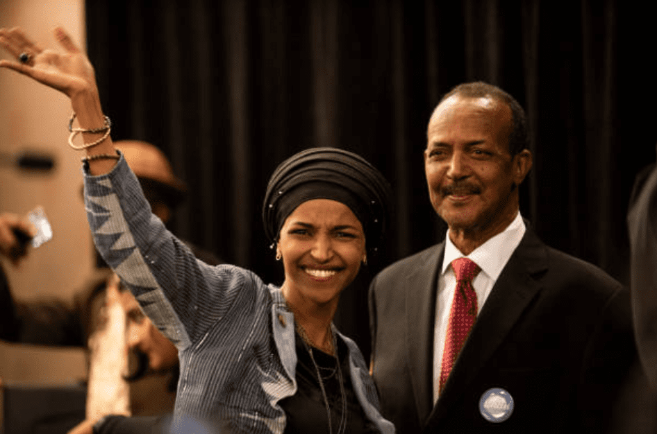 Ilhan Omar waves to supporters while standing with her father Nur Omar Mohamed on November 6, 2018, in Minneapolis, Minnesota | Source: Stephen Maturen/Getty Images