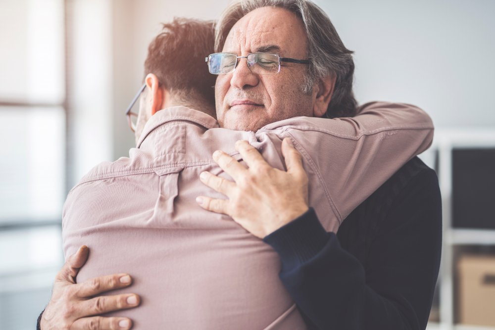 A photo of a young man hugging an older man | Photo: Shutterstock