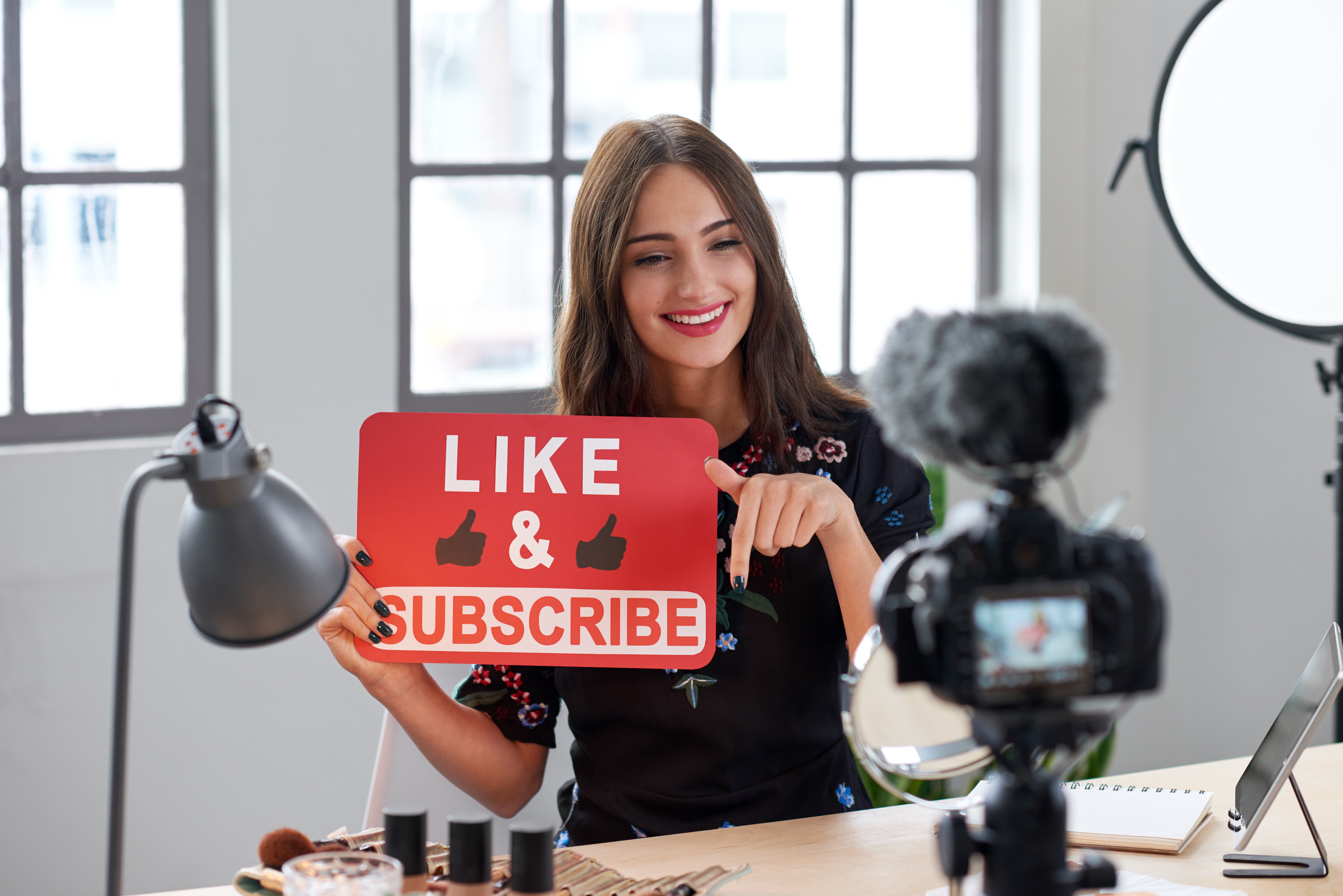 """Young woman holding a """"Like & Subscribe"""" placard while recording herself.   Source: Shutterstock"""