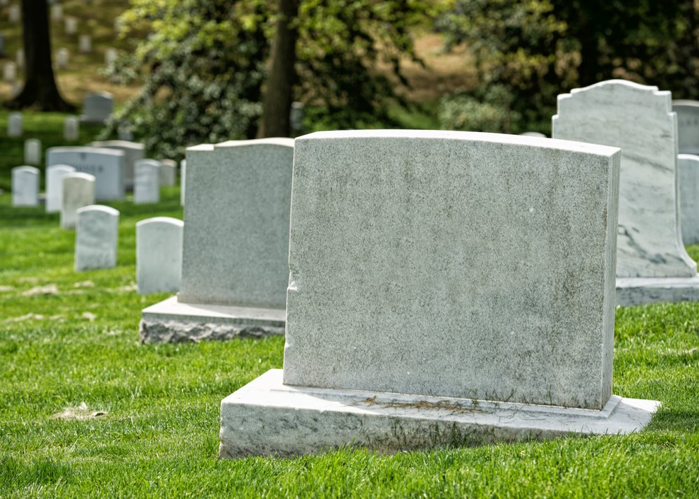 A cemetery graveyard with white tombstones. | Photo: Shutterstock