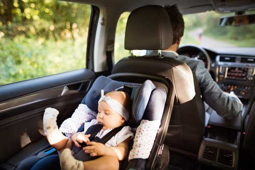 A father driving with his baby in the car. | Source: Shutterstock.