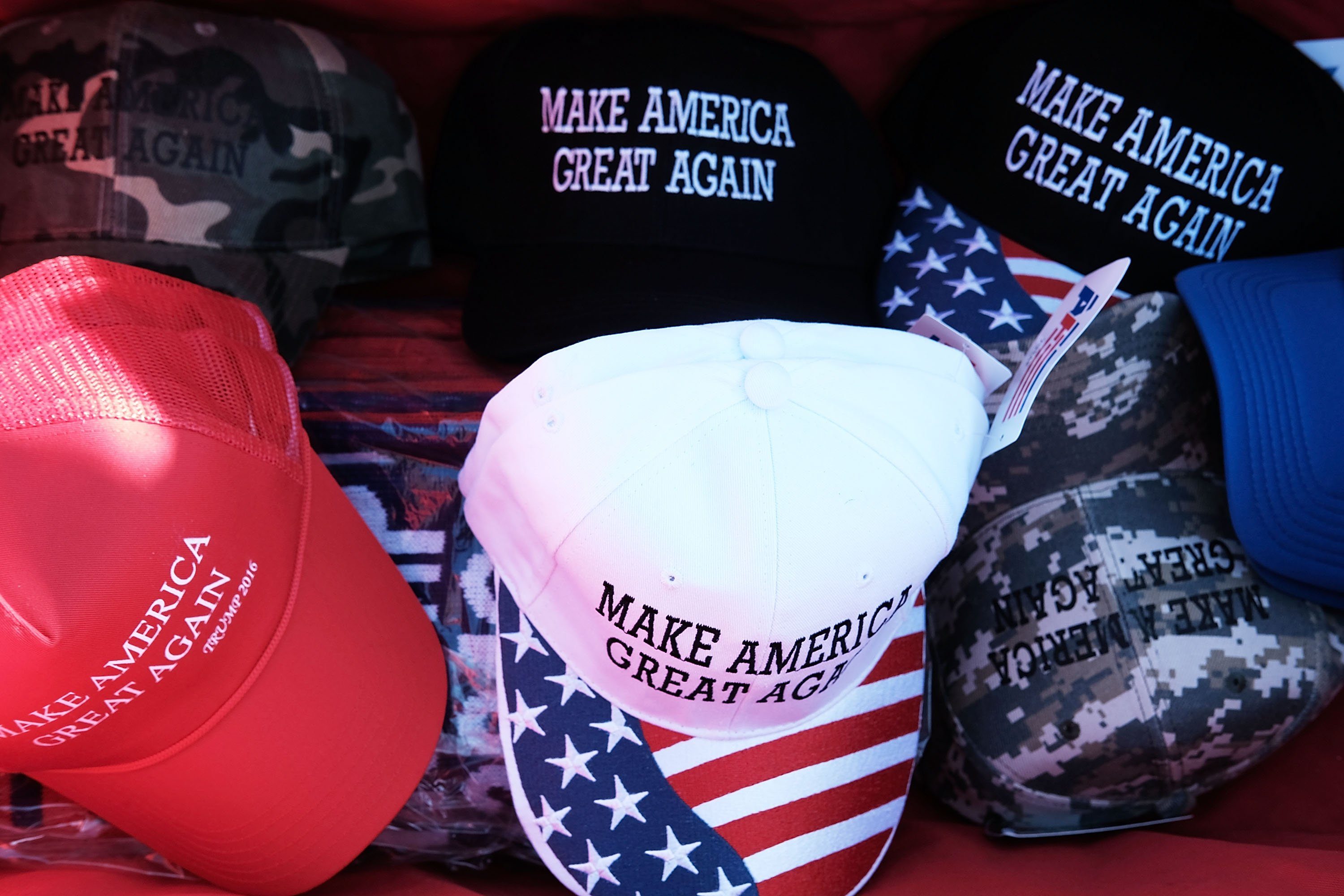 Different styles of MAGA hats being sold at a rally | Photo: Getty Images