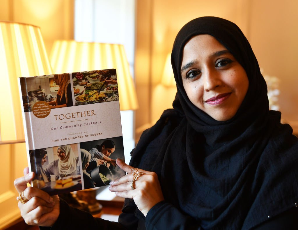 Zahira Ghaswala hols a copy of 'Together' a book that tells how women came together after the Grenfell Tower tragedy to cook for the local community, which has a foreword by the Duchess of Sussex at Kensington Palace. | Photo: Getty Images