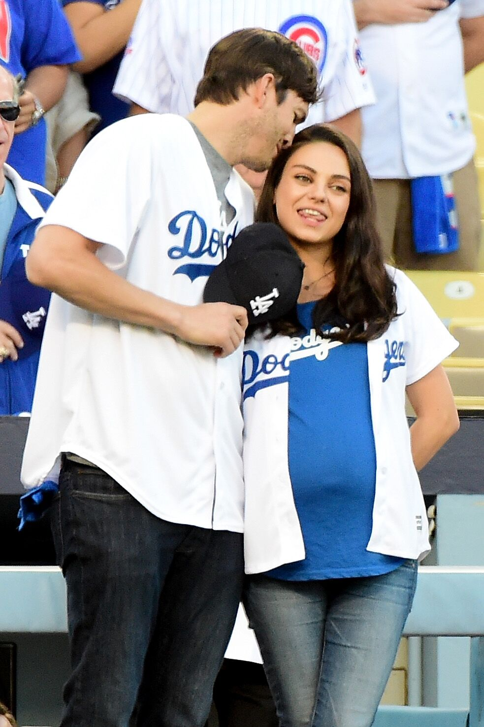 Ashton Kutcher and wife Mila Kunis on the field after they announced the Los Angeles Dodgers starting lineup before game four of the National League Championship Series | Getty Images