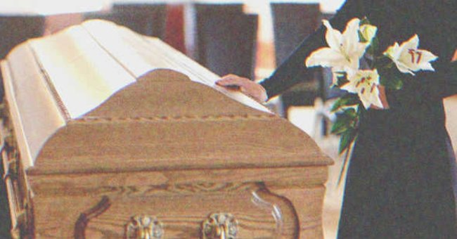Woman holding flowers and touching a funeral casket   Source: Shutterstock