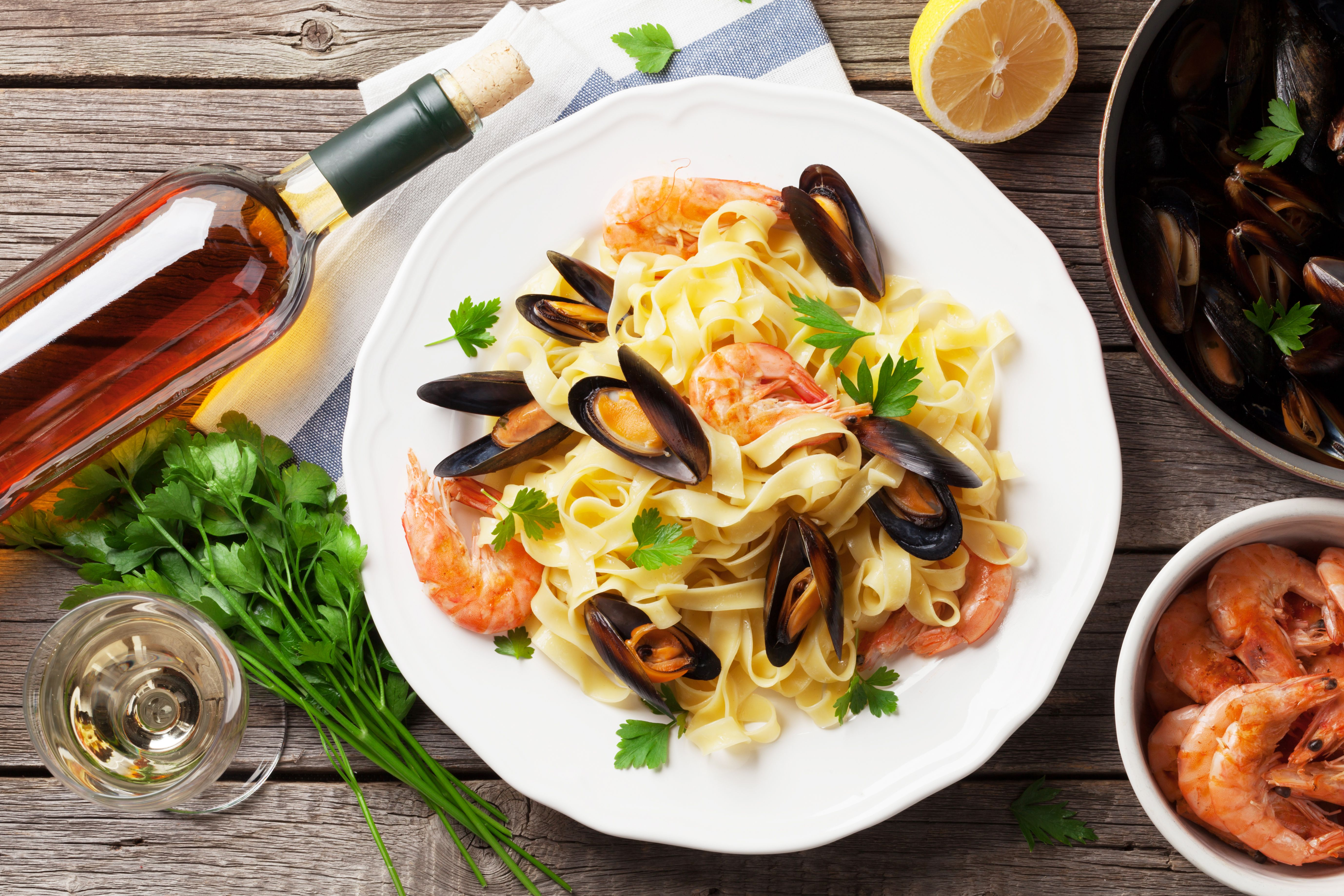 An assortment of seafood with a bottle of wine. │ Source: Shutterstock